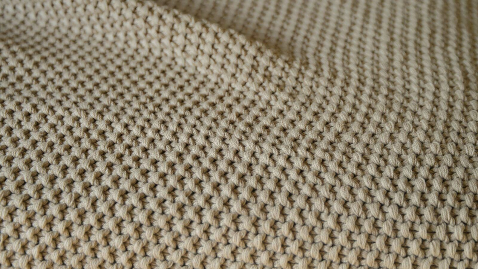 moss stitch knitted cotton throw in taupe