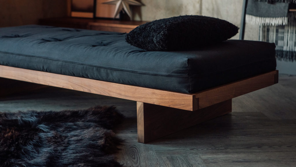 A close-up of the solid walnut Kyoto Daybed with futon mattress, all hand made in Britain