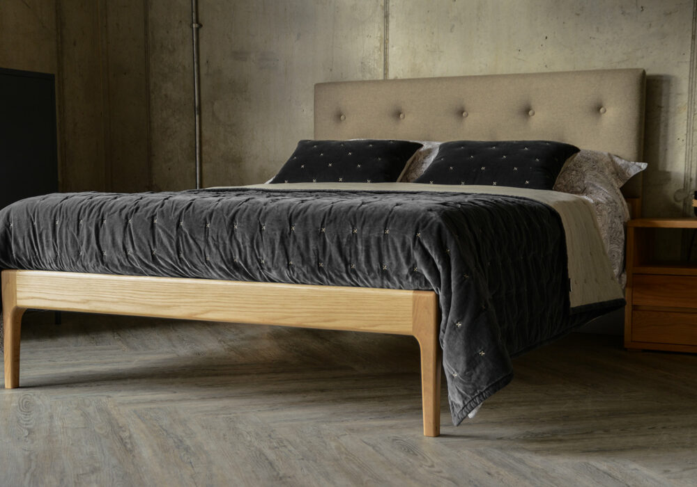 Upholstered solid oak hand crafted bed with soft grey velvet quilt