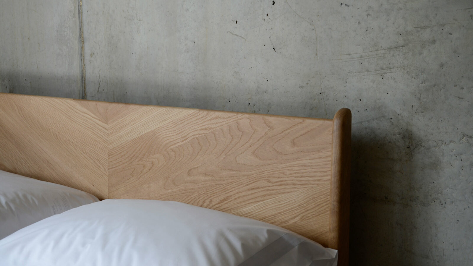 A closer view of the chevron design solid wood headboard of the Oak Hoxton bed