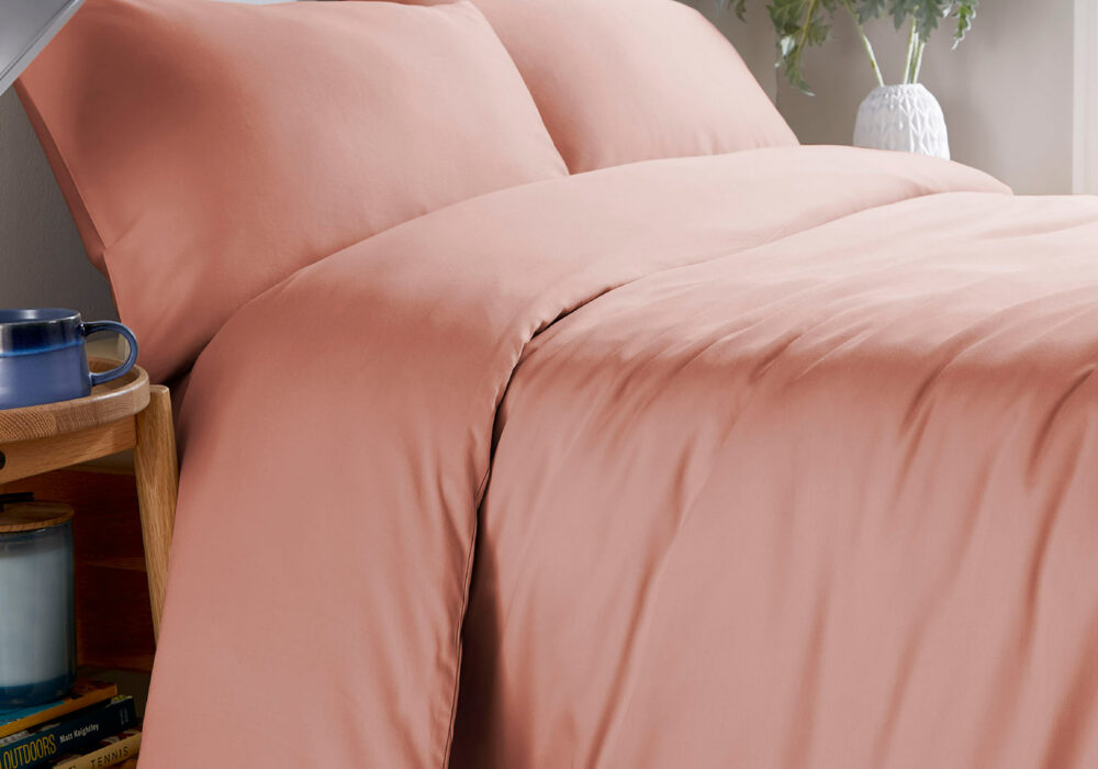natural blush pink coloured organic cotton bedding 300 thread count shown on a bed