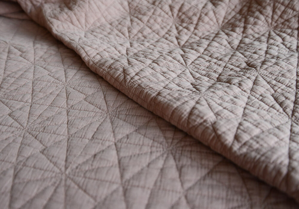 detail shot of the blush pink hexagon Stitched quilted bedspread