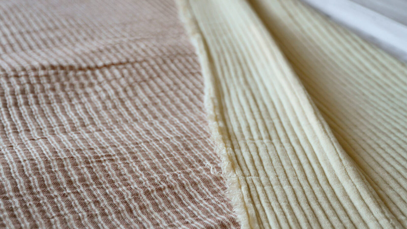 reversible textured cotton bedspread pink striped one side plain cream reverse a close-up view