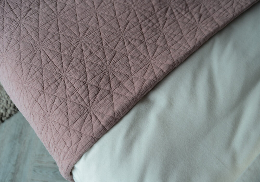 close up view of the blush pink hexagon quilted bedspread