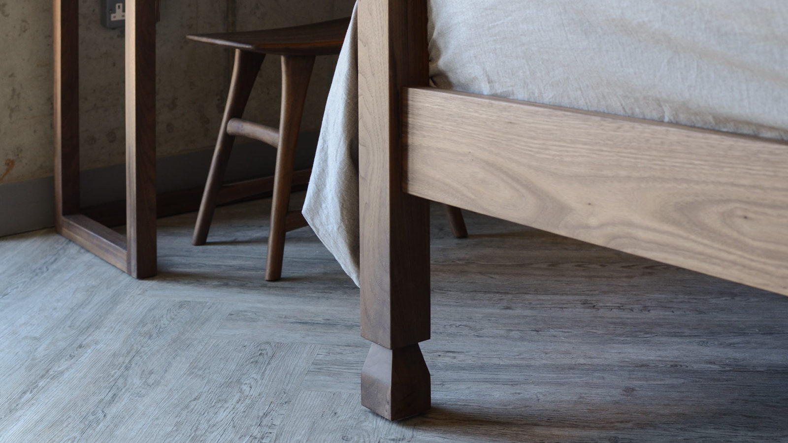 A detail view of the Raj 4-Poster Bed carved leg, shown in Walnut but comes in a choice of wood