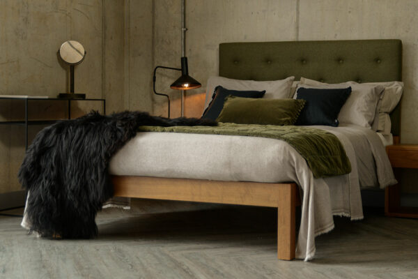The Skye bed made in walnut with a tall buttoned wool-upholstered headboard