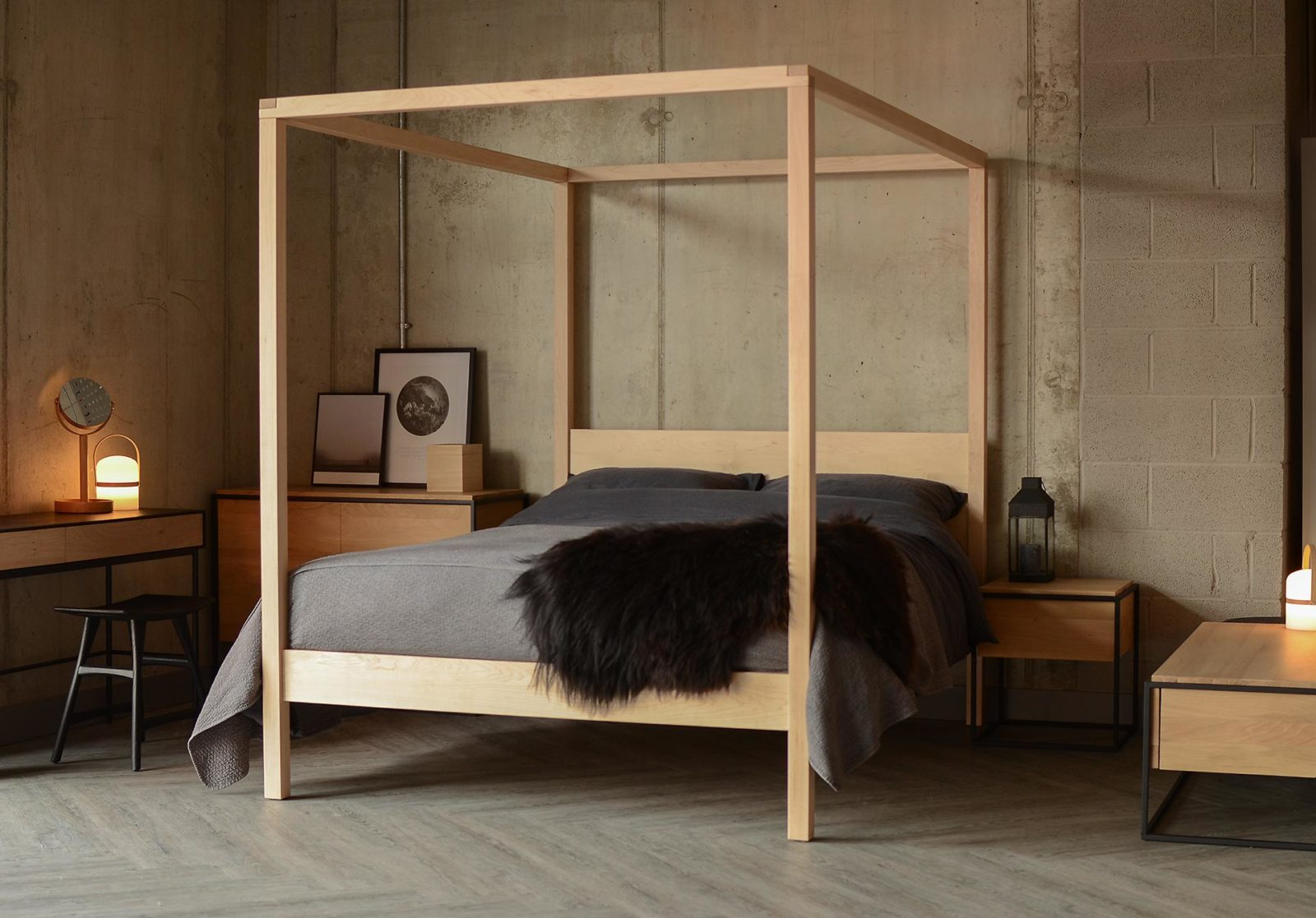 A contemporary handcrafted 4 poster bed this Orchid bed in Maple with dark bedding has a Scandinavian style