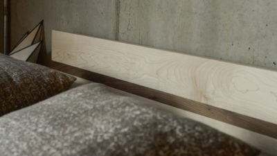 A closer view of the Tibet wooden bed headboard in Maple with a Walnut stripe