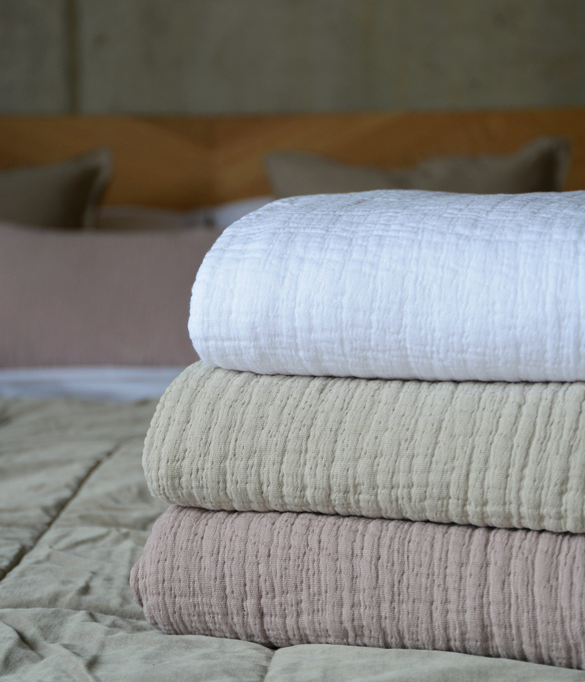 pure cotton crinkled effect throws up close and in white and stone