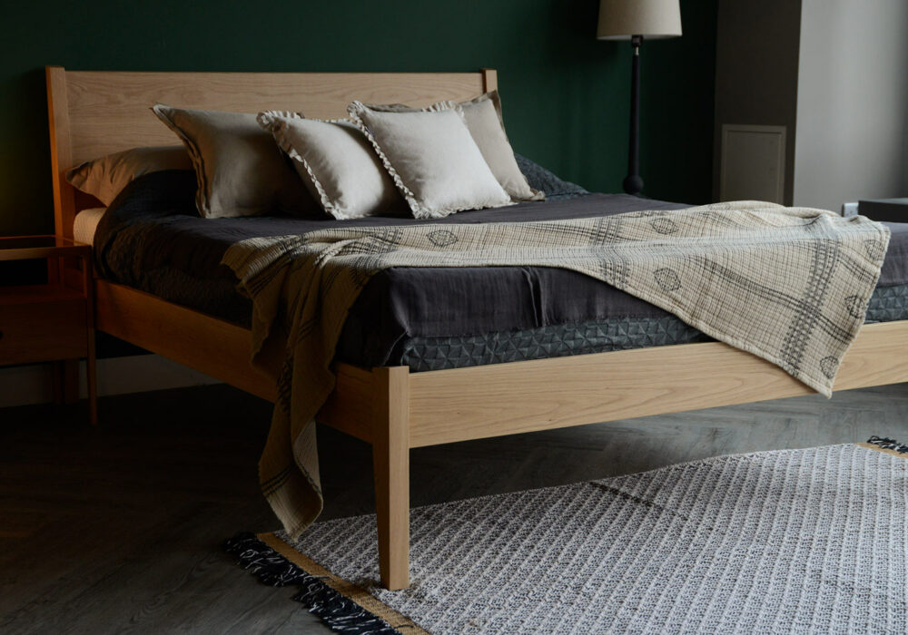 Contemporary classic a kingsize Zanskar bed in solid oak shown with neutral bedding