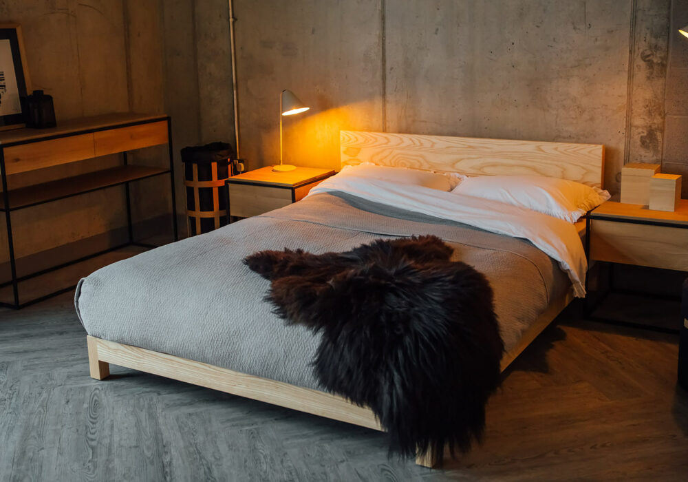 Scandinavian bedroom style with our low wooden Sonora bed in Ash and with sheepskin throw