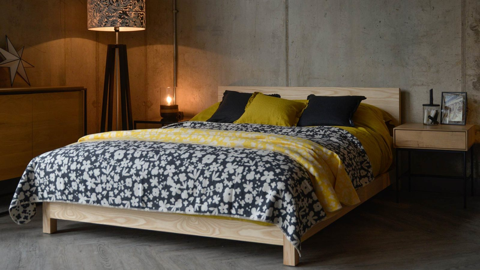Modern floral Marimekko style cotton rich soft throws in charcoal and yellow shown on Sonora low wooden bed
