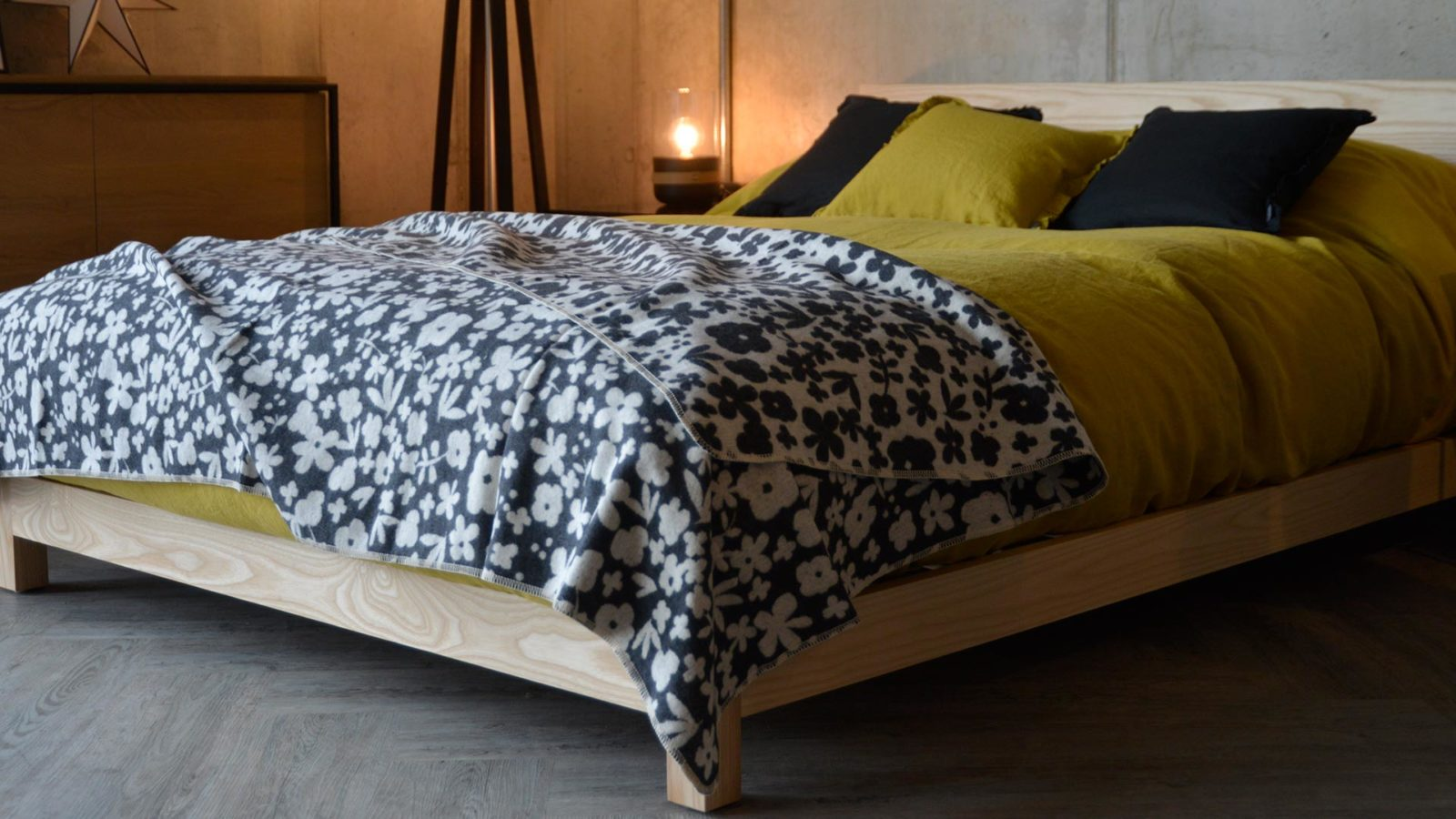 Modern floral Marimekko style cotton rich soft throw in charcoal shown on Sonora low wooden bed