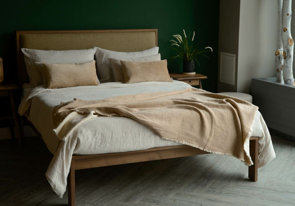 organic cotton reversible throw in beige and ivory shown on a kingsize bed