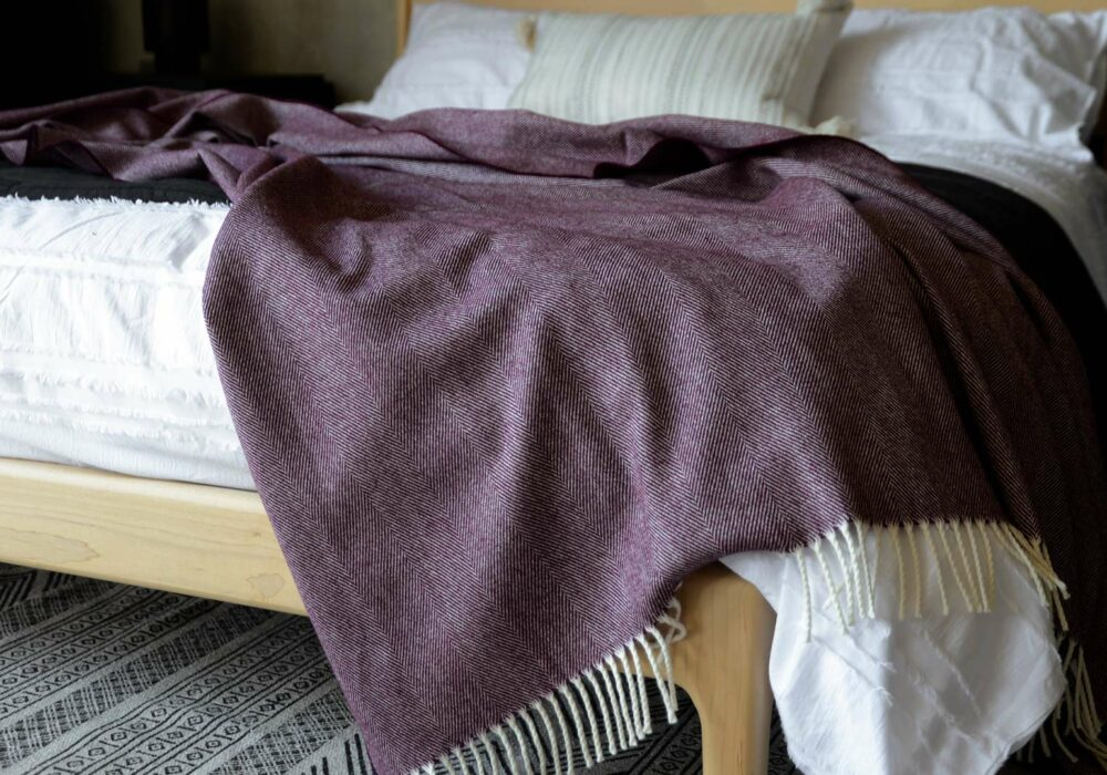 large herringbone weave merino wool throw in berry and ivory a close up view