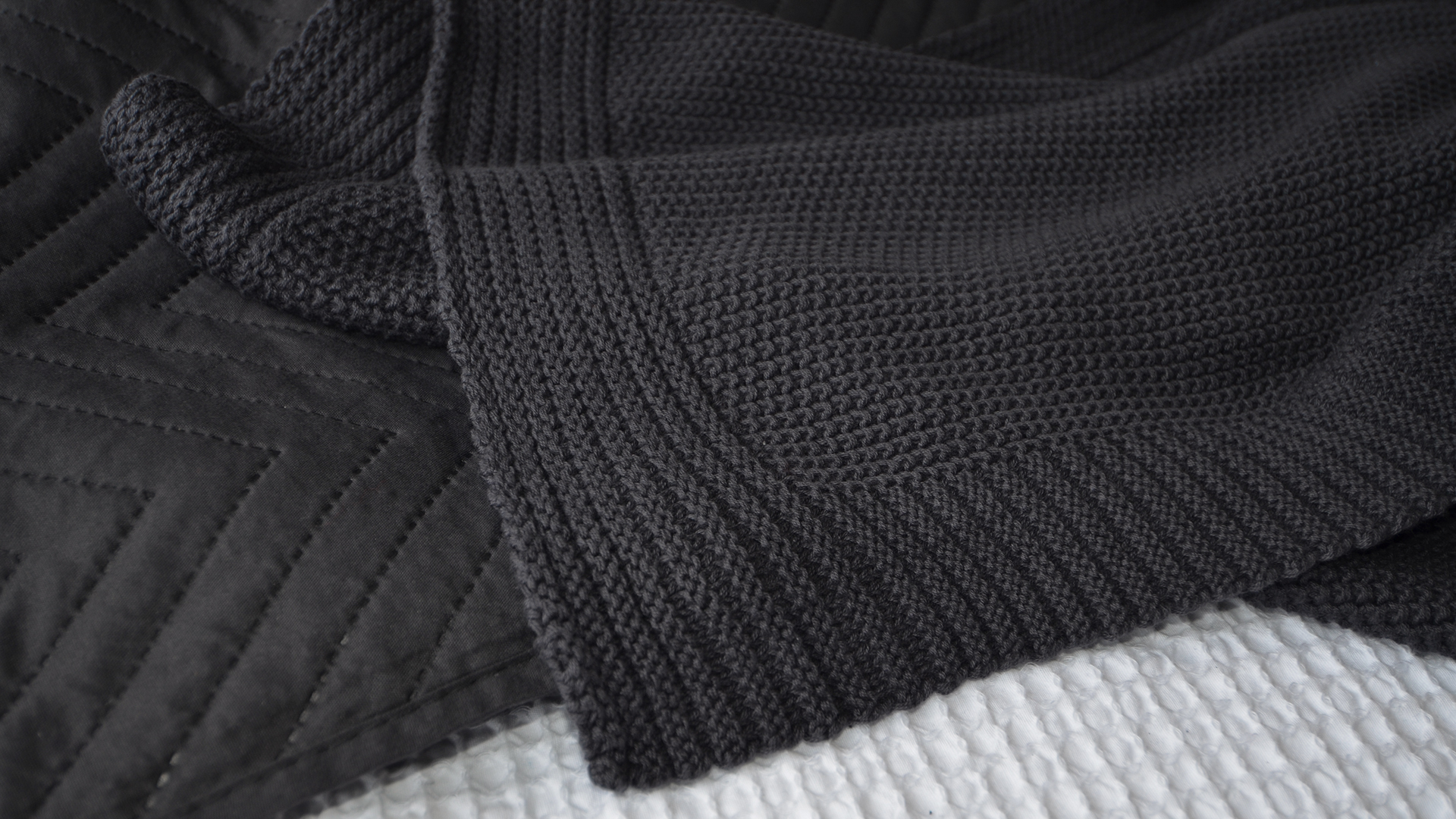 black bedspread and black knitted throw