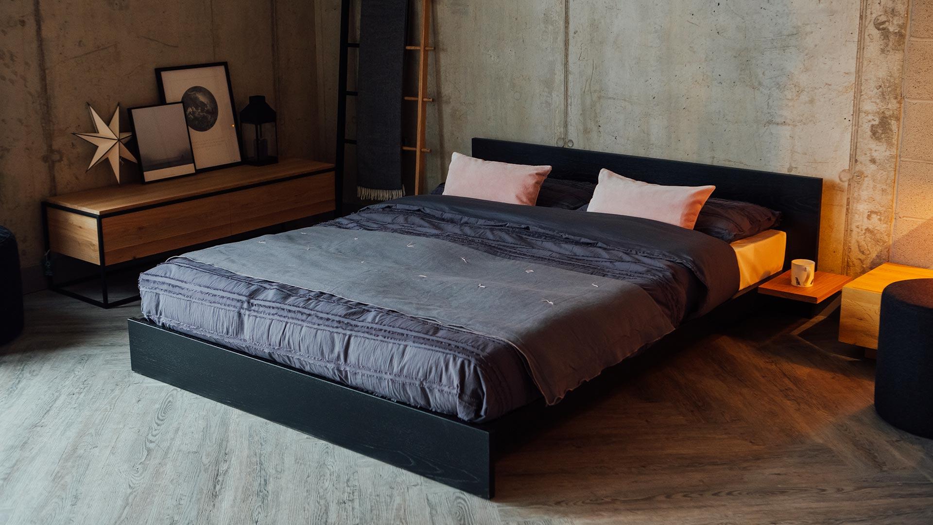 Low wooden Kulu bed in black painted Oak with contrasting Oak side tables.