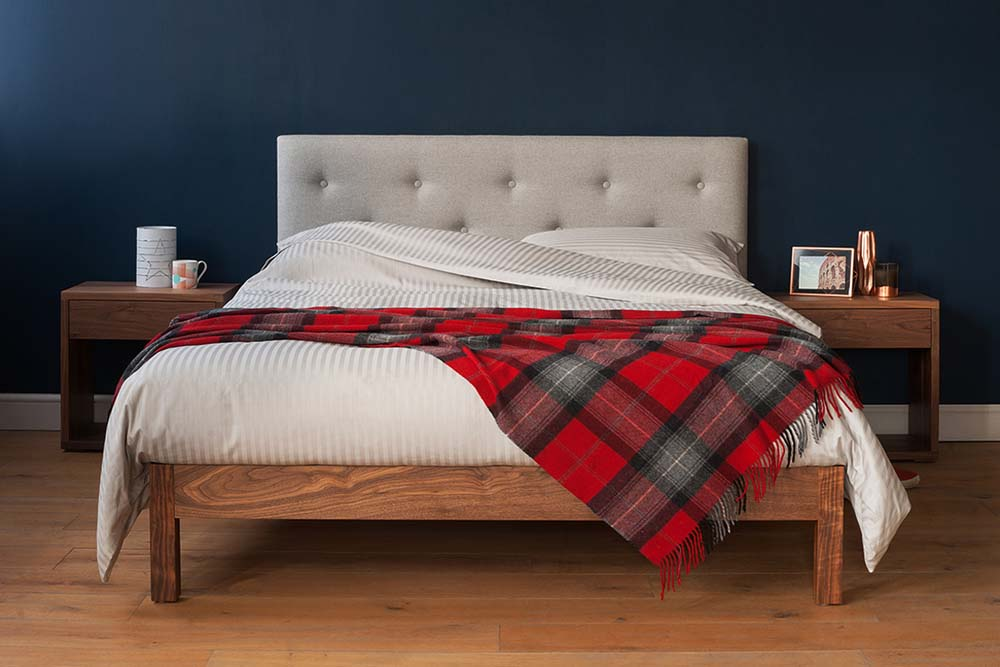Woollen red-checked throw gives the Arran bed with grey upholstered headboard a seasonal look