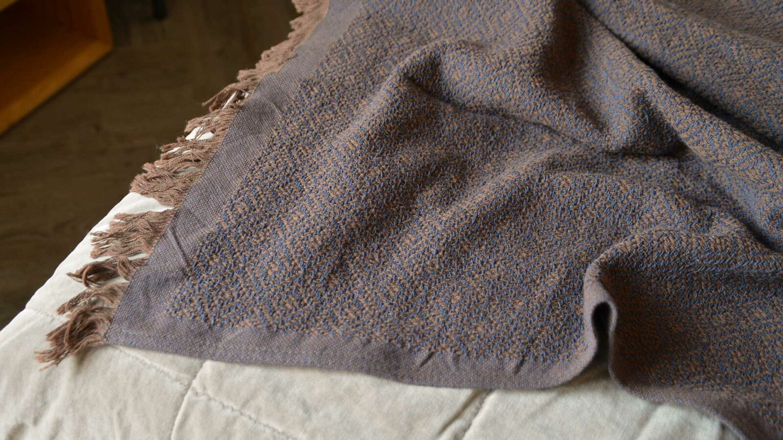 cotton rich woven diamond pattern throw in russet brown and blue