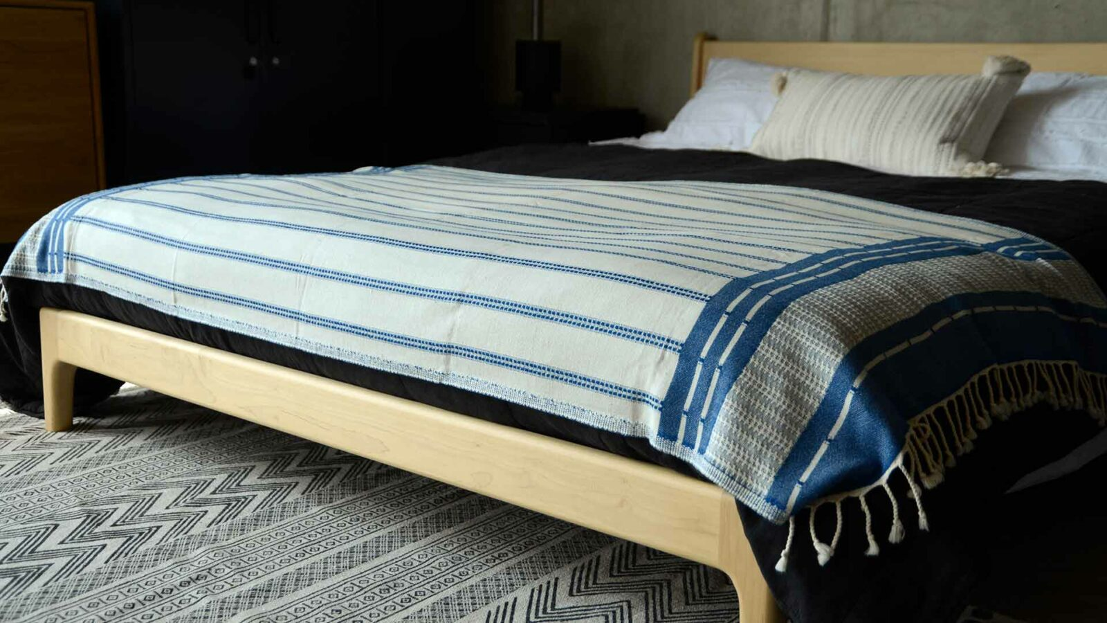 reversible blue and ivory coloured woven cotton throw shown on a bed