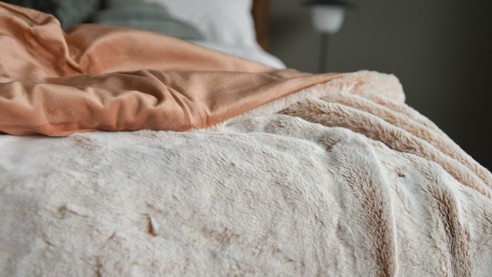 Frosted pink faux fur throw a view showing the reverse salmon pink velveteen fabric