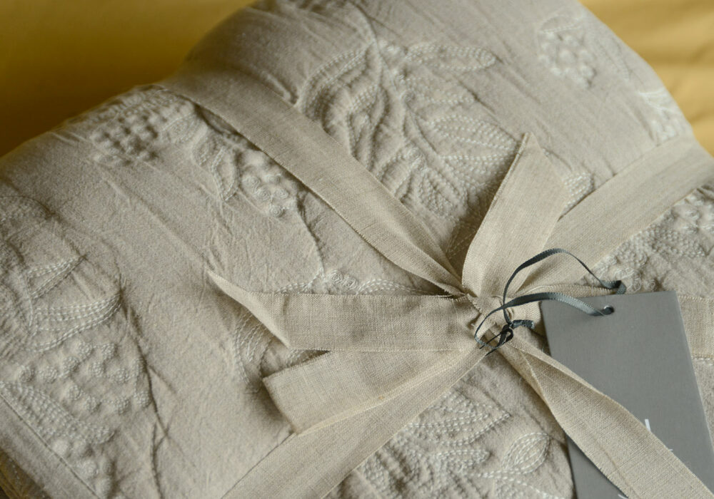 Embroidered quilted bedspread sand coloured one side ivory reverse, shown close up