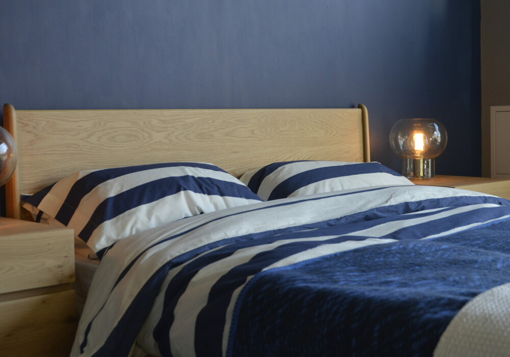 A closer view of the Carnaby bed headboard in Oak, shown with navy & ivory striped cotton duvet set.