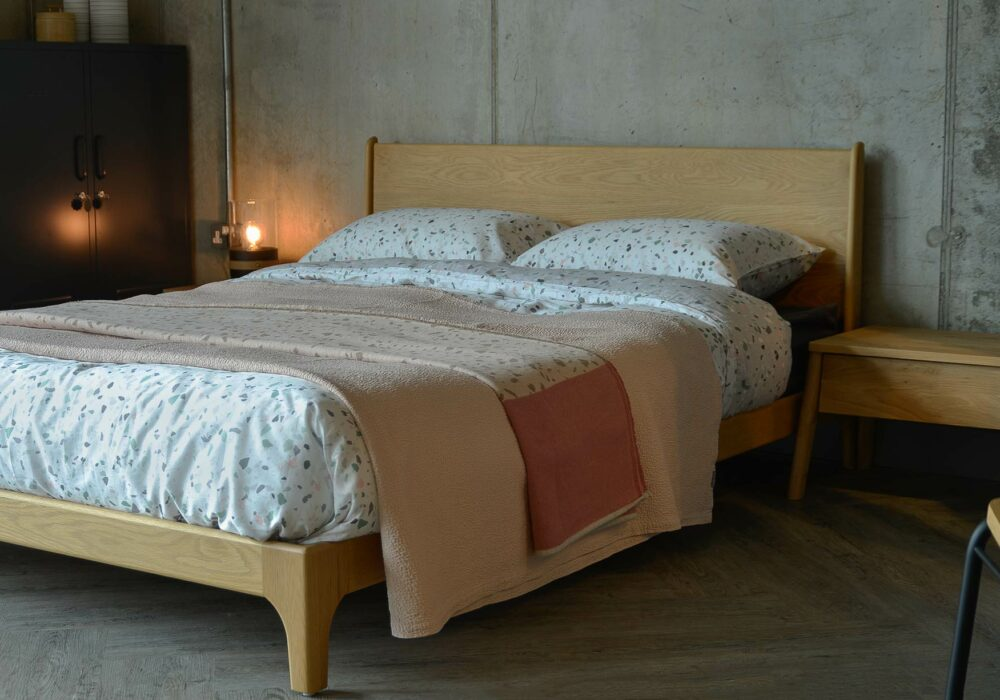 The Carnaby low oak bed from Natural Bed Company is dressed with terrazo print bedding and a cotton bedspread.