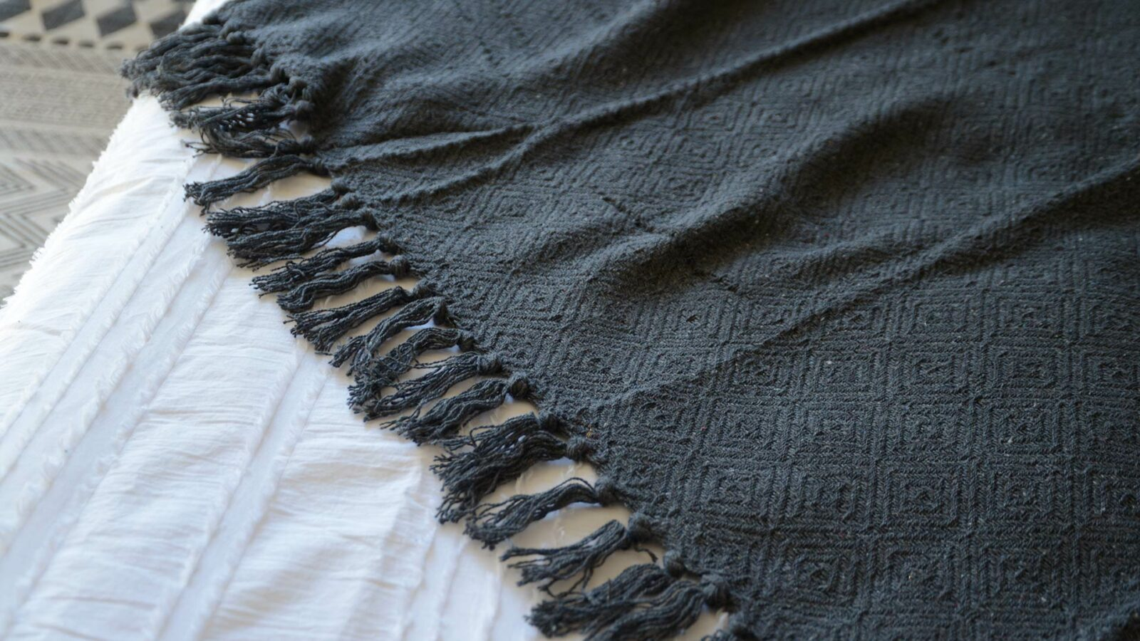 charcoal grey diamond weave cotton throw with fronted edge shown close up