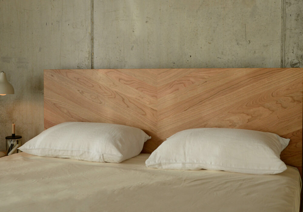 the parquet patterned headboard of our Hathersage solid wooden bed in cherry