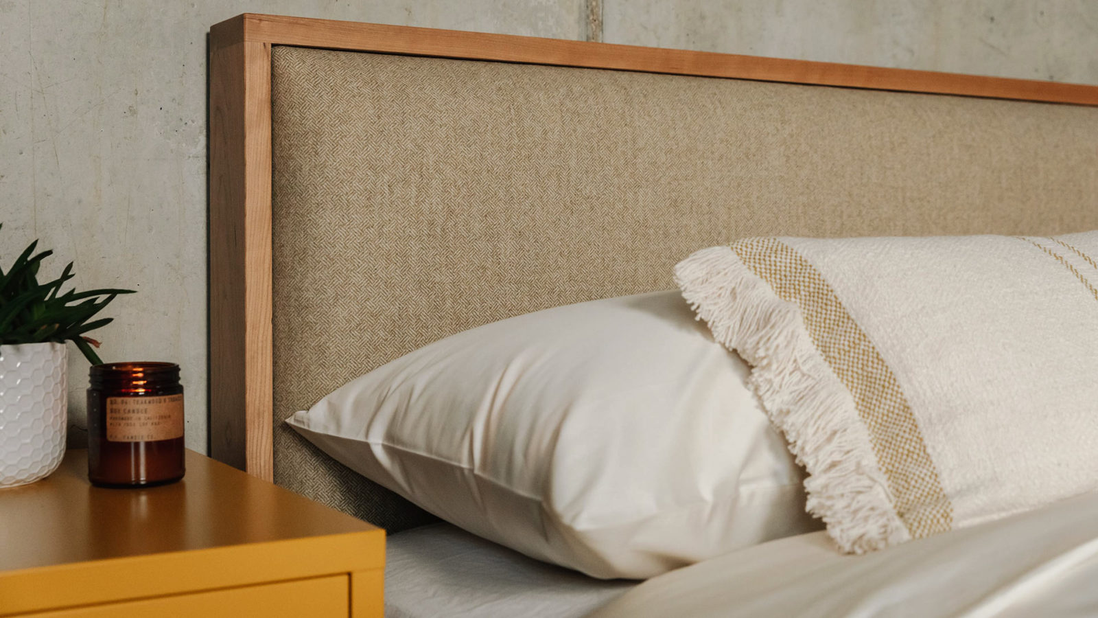 The upholstered headboard of the Shetland contemporary wooden bed in cherry