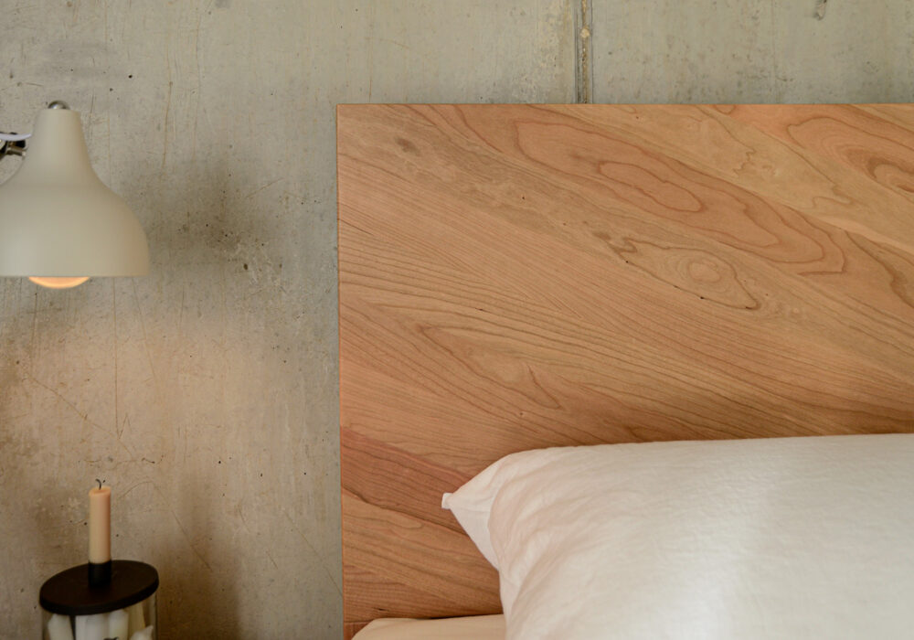 Detail view of the parquet pattern wooden headboard of the cherry Hathersage bed