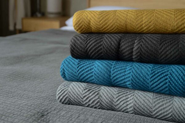 stack of soft knitted chevron pattern throws in a range of colours