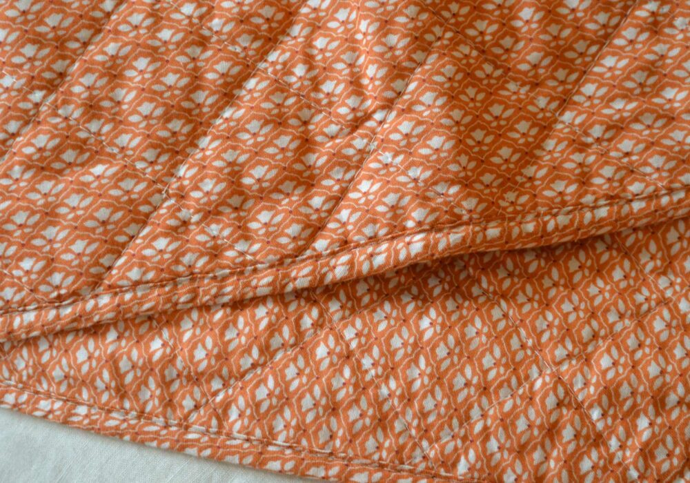 orange quilted throw with a delicate ivory flower pattern, a close-up view