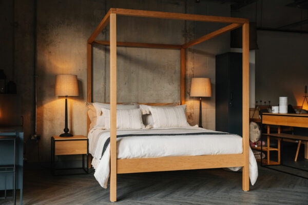 softening an industrial bedroom, luxurious layered bedding and oak wooden 4 Poster bed