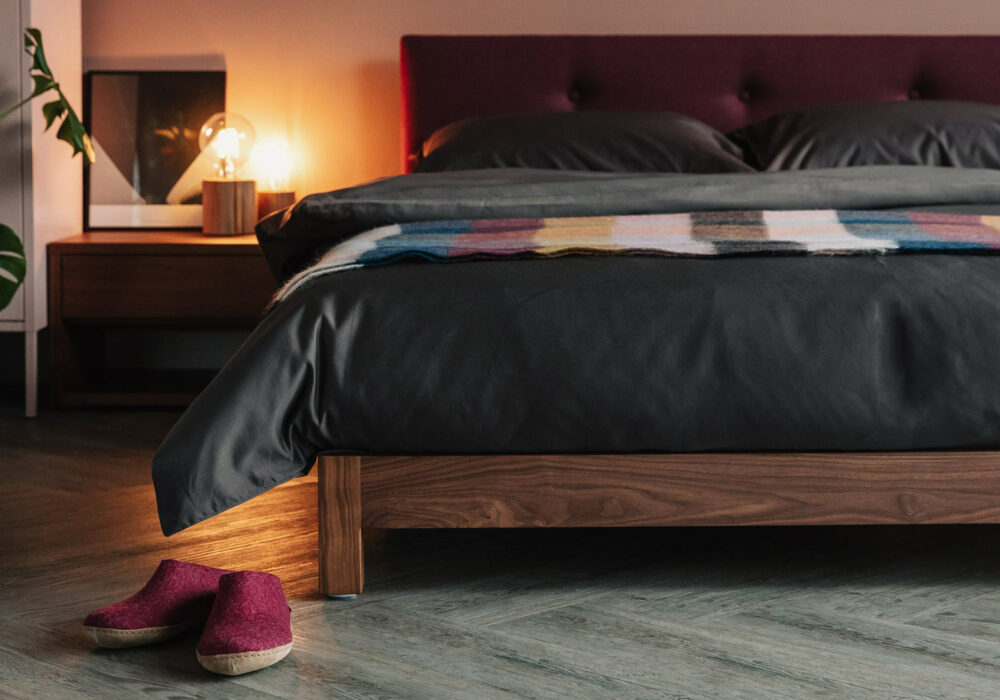 Iona a low wooden bed with buttoned upholstered headboard. This one is in Walnut wood.