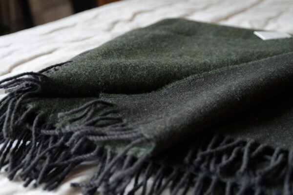 reversible pure wool throw in Fir Green and slate grey shown close up