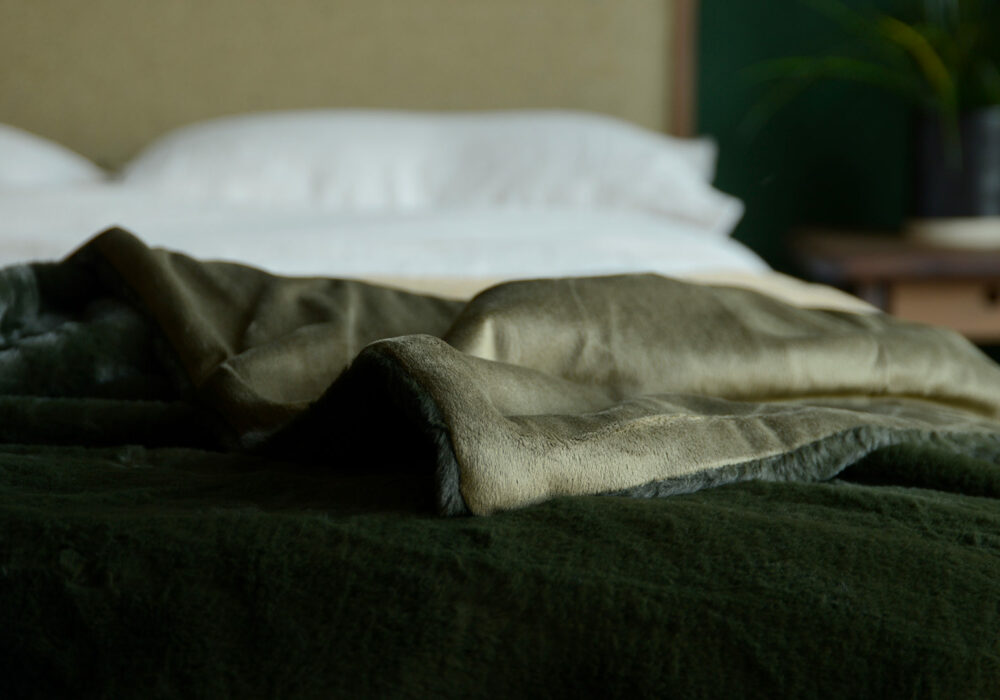 a closer view of our softest faux fur bed throw in deep olive green