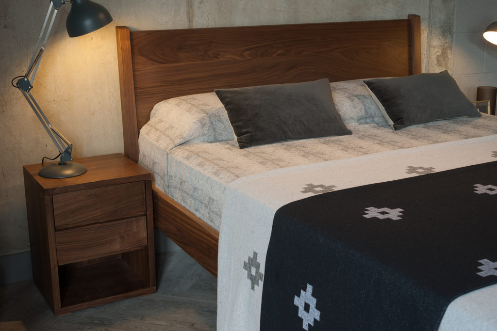 A view of the headboard of our walnut Zanskar bed shown with 2 drawer cube bedside table.