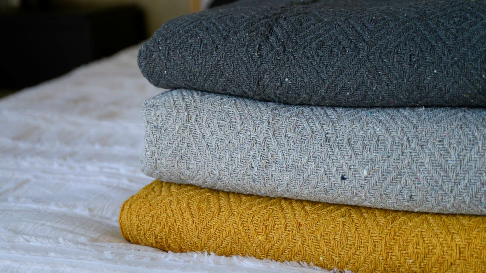 diamond weave cotton throws in 3 colour ways shown close up and stacked
