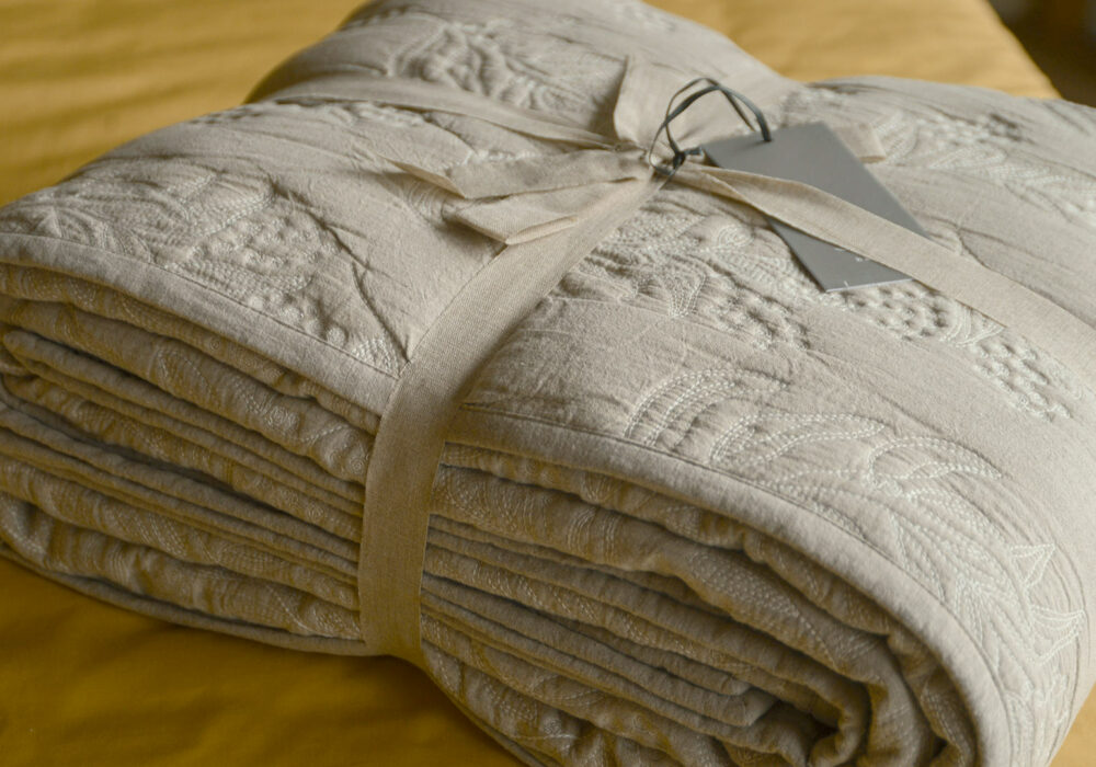 Reversible stitched and quilted bedspread ivory one side beige the other shown folded