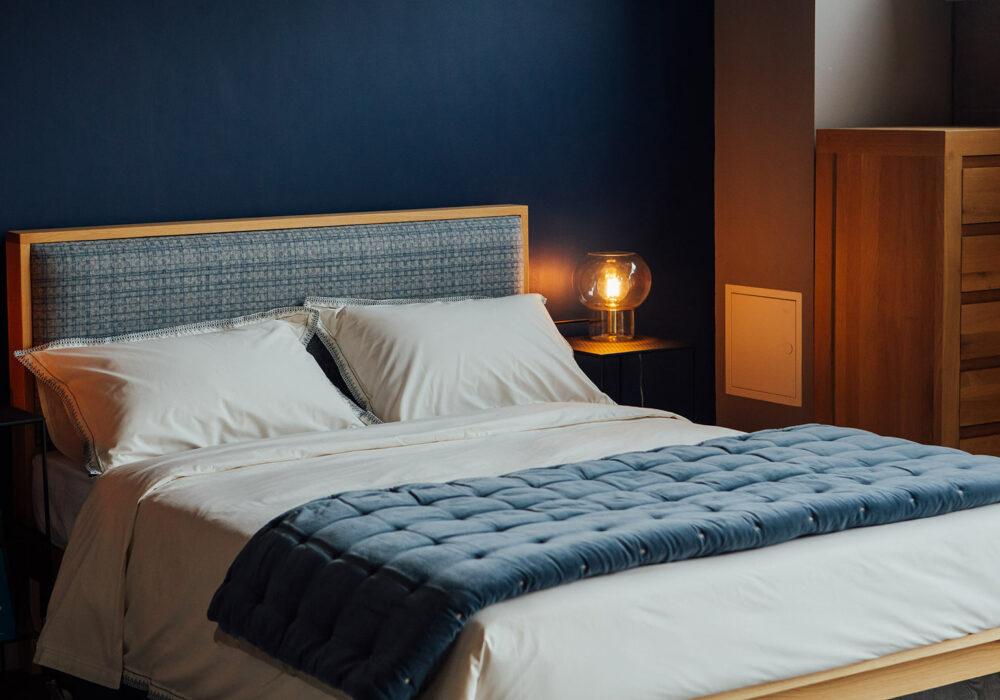 Blue patterened wool headboard on our wooden Shetland bed in Oak