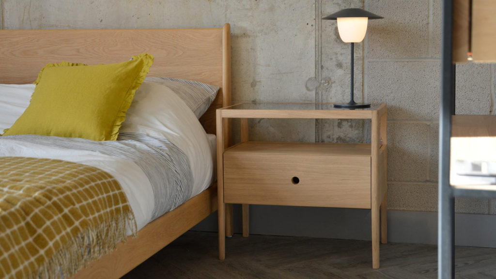 Spindle is an Oak bedside table with storage drawer and open shelf. It is shown with our mid-century style Oak Carnaby bed.