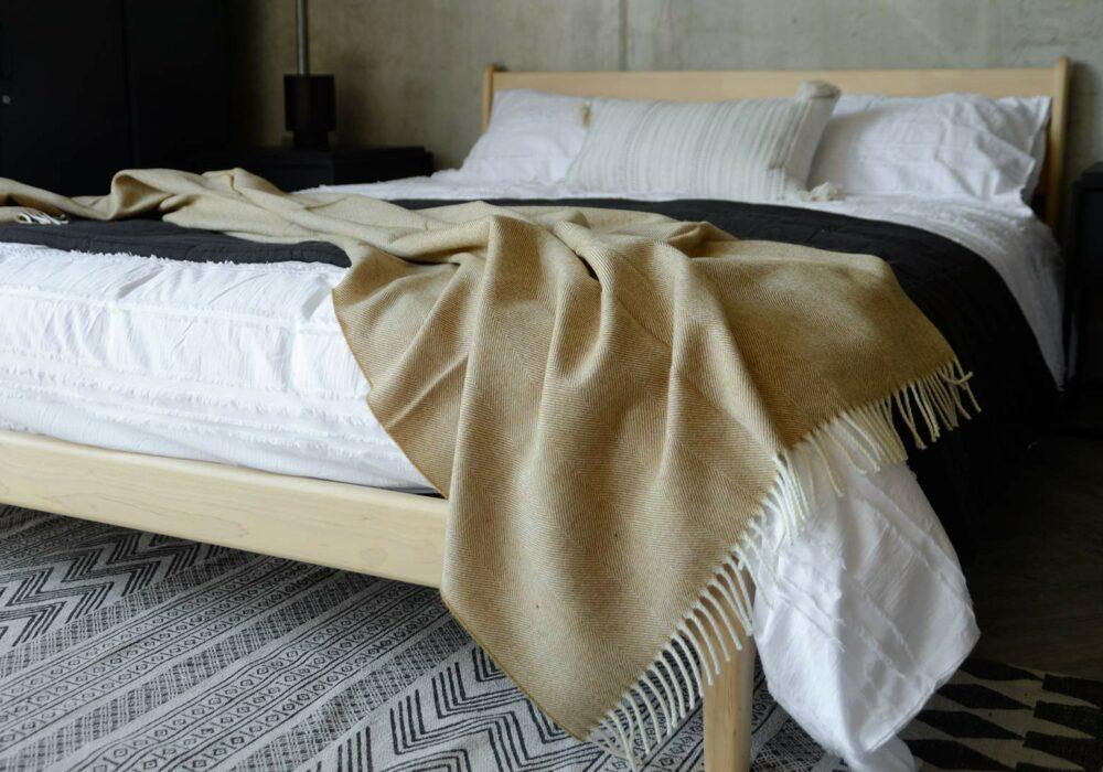 large herringbone weave merino wool throw in caramel shown on a kingsize bed