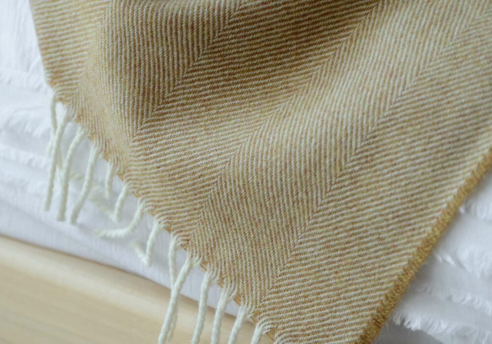 Large herringbone weave merino wool throw in caramel and ivory a close up view
