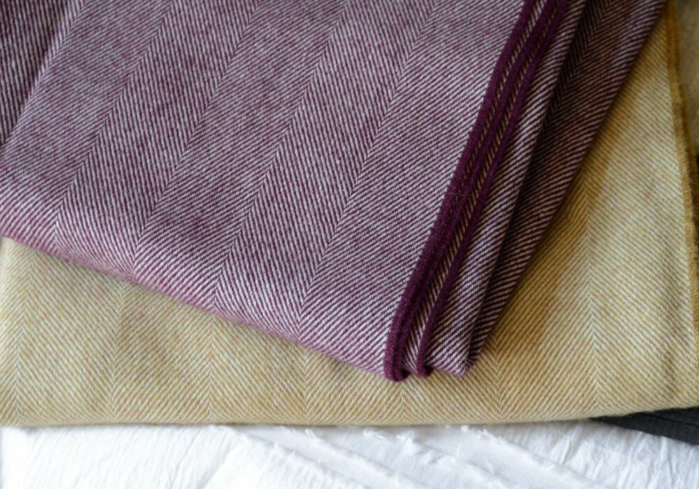 large herringbone weave merino wool throws in berry and caramel colour options, a close up view