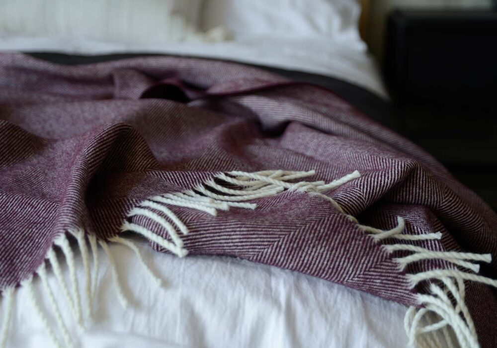 large herringbone weave merino wool throw in berry and ivory, a close up view