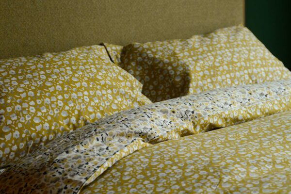 modern blossom patterned reversible duvet cover set in yellow, white and grey shown on a bed