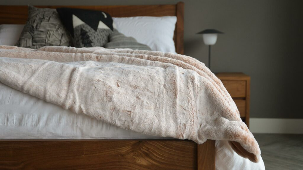 Frosted pink coloured faux fur throw on our walnut Cochin bed