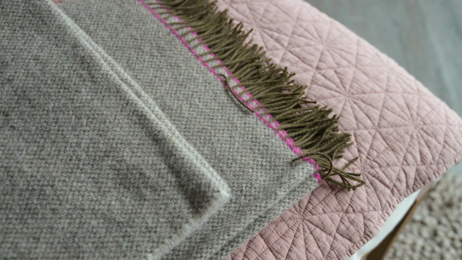 woven pure wool throw in greys with bright pink contrast edge